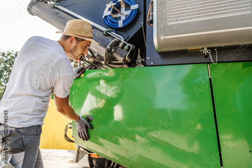 Pinturas sobre lienzo  The mechanics repair the yellow combine harvester in the farm yard