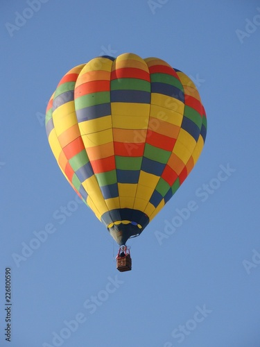 hot air balloon flying in blue sky with yellow orange red green and blue colors