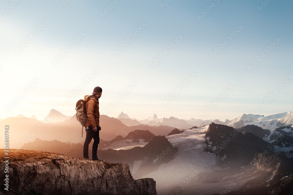 Fototapety, obrazy: Rear view of a man standing on the cliff against sunset