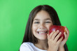 canvas print picture - Happy child girl eat apple isolated on green background. Kid with fruits.