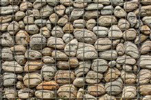 Wall Made Of Round Rocks, Secured With Steel Wire Net (iron Stone Gabion)