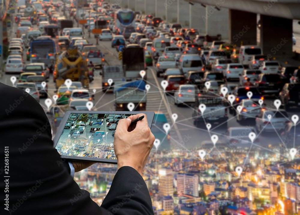 Fototapeta Businessman holds a tablet car on the road network technology of digital map in the city