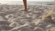 Carefree female tourist runs barefoot along the beautiful ocean in the warm sand. Unknown girl jogging on the sunny tropical beach on stunning paradise island. Slow motion Low angle Close up