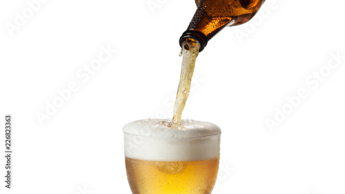 Fotografie, Obraz  A bottle pours cold beer in a glass, isolated on withe background