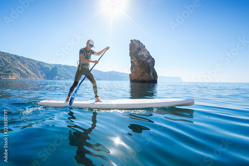 Stand up paddle boarding. Young man floating on a SUP board. The adventure of the sea with blue water on a surfing