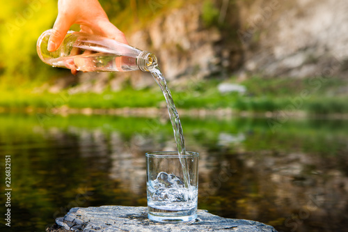 Fotobehang Hand Holding Drinking Water Glass Bottle And Pouring Water Into Glass On Stone On Blurred Green Bokeh Nature Background. Toned.