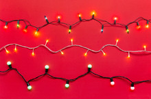 Christmas Light Bulbs And Led Lights On String In Multi Colours; Warm White, Blue, Yellow, Green, Pink & Red On Vivid Red Velvet Background For Xmas Tree Decoration Or New Year Celebration Events