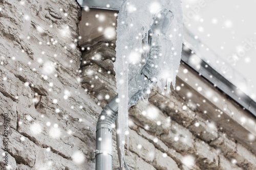 Valokuva  season, housing and winter concept - icicles hanging from building drainpipe