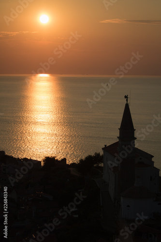 aerial view on church silhouette in golden sunset in Piran, Slovenia