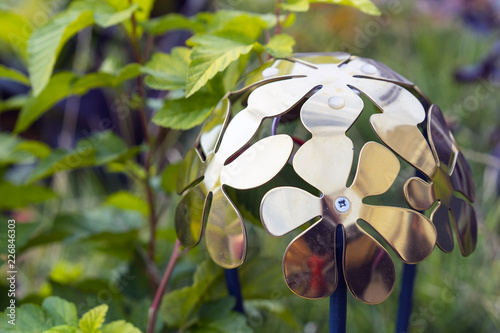 Photo  Metal lantern with floral design in green garden.