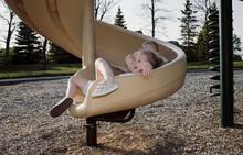 Two Girls Sliding Down Spiral Slide At Playground