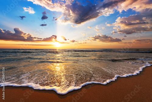 Obraz na plátně Colorful ocean beach sunrise with deep blue sky and sun rays.