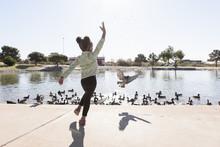 Full Length Of Playful Girl Feeding Birds In Lake During Sunny Day At Park