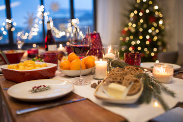Obraz na Plexi christmas dinner and eating concept - glass of red wine and food on table at home