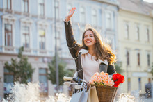 Young Woman Walking With Bicycle And Waving Hand