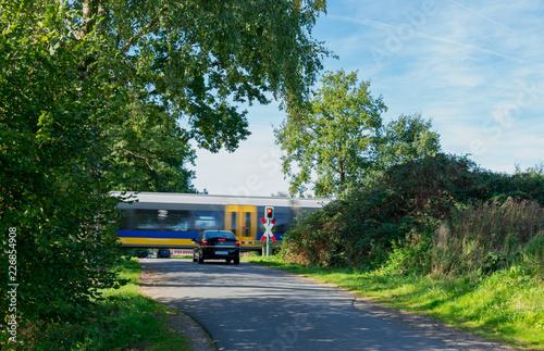 Fotografia, Obraz  Bahnübergang mit wartendem Auto und vorbeifahrendem Zug