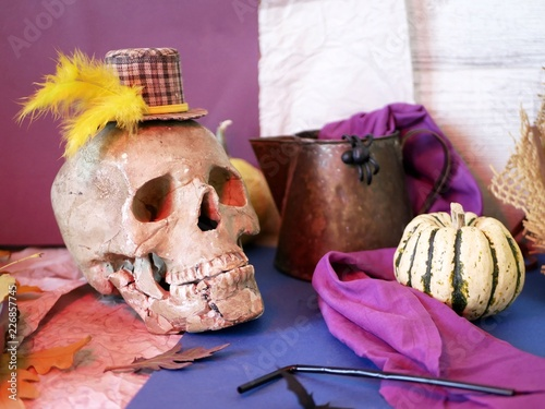 Foto  Seasonal decorative still life from pumpkins, skull, jug, purple cloth, black p