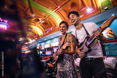 Leinwand Poster Smiling man and woman playing the guitar game at a gaming arcade