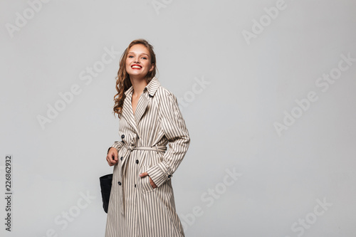 Fotografija Young pretty cheerful woman with wavy hair in striped coat happily looking in ca