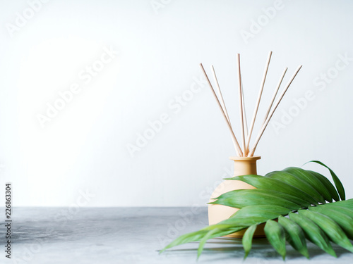 Fotografía  aroma reed diffuser home fragrance with rattan sticks on a light background with palm leaves and shadows