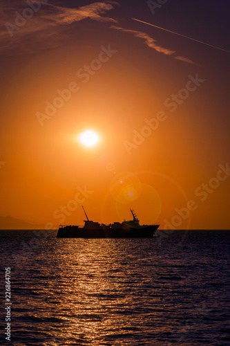 Large ferry boat at sunset on the Aegean Sea leaving Samothrace Island in Greece at sunset