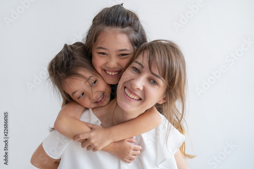 Foto  Happy multiethnic sisters hugging mother from behind with love and smiling widely