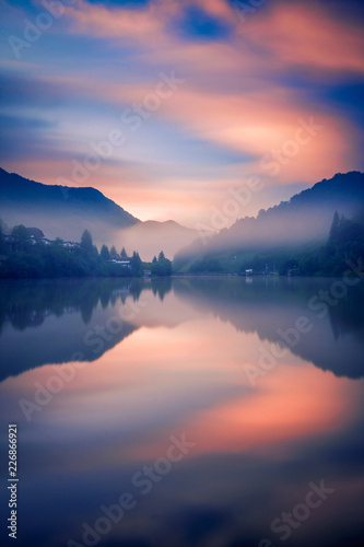 Fotografía  Foggy morning on a lake in the mountains with some houses on the shore shot with