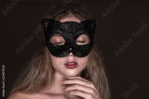 Beautiful young tender woman posing isolated over dark beige chocolate  brown background wall wearing carnival cat masquerade mask eyes closed. 1905ab281d9