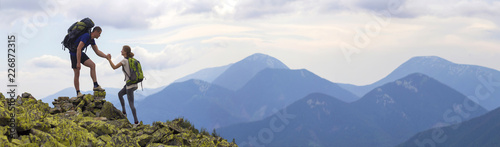 Spoed Fotobehang Alpinisme Young tourists with backpacks, athletic boy helps slim girl to clime rocky mountain top against bright summer sky and mountain range background. Tourism, traveling and healthy lifestyle concept.