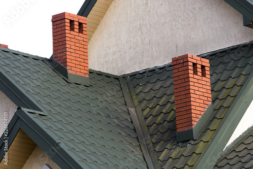 Close-up detail of new modern house top with shingled green roof, high brick-red chimneys and stucco walls Fototapet