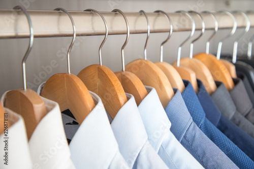 Valokuvatapetti Office Business shirts hanging on wooden hangers ordered by colour