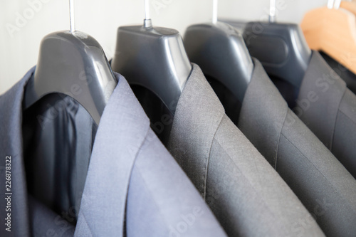 Valokuva Office Business suits hanging in a closet ordered by colour