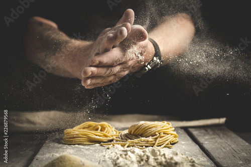 A man claps his hands and sprinkles flour on fresh pasta Fototapete