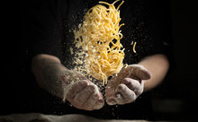 Close Hand Make Pasta Toss On A Black Background Before Cooking The Dish
