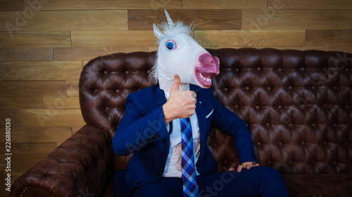 Fotografie, Obraz Funny unicorn in elegant suit sits on sofa like a boss and showing gesture thumbs up