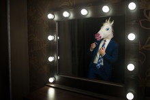 Glamour Guy In Elegant Suit And Comical Mask Looks At Himself In The Mirror In Dressing Room. Freaky Young Man In Stylish Room Posing Like A Boss. Unusual Unicorn.