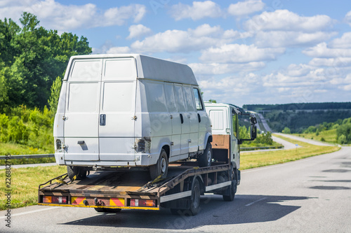 Light truck - tow truck, transports a white, damaged, broken minibus on itself along a highway between cities against a blue summer sky with white clouds .