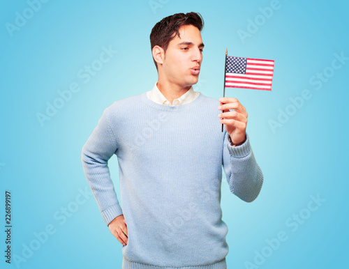 Photo  young handsome tanned man with an usa flag