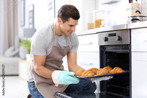 Man taking baking tray with delicious croissants out of electric oven in kitchen