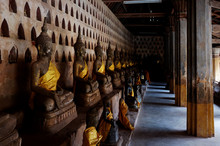 Gold Plated Theravada Buddhist Statues At A Monastery With A Yellow Silk Cloth