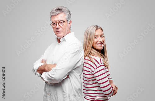 Fotografie, Obraz  senior cool husband and wife standing sideways, with a proud, satisfied and happy look on face, smiling with arms crossed