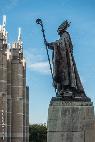 In de dag Historisch mon. Brussels, Belgium - September 26, 2018: Bronze statue of Catholic Cardinal Mercier on stone pedestal against blue sky looking at office building and against blue sky.