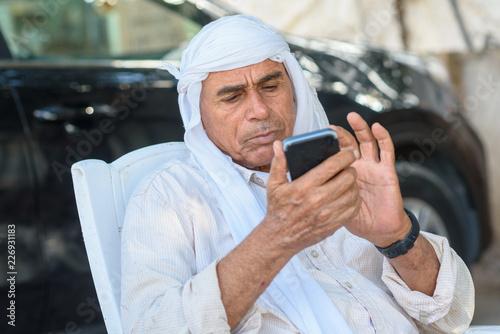 Muslim Senior businessman using a smartphone Wallpaper Mural