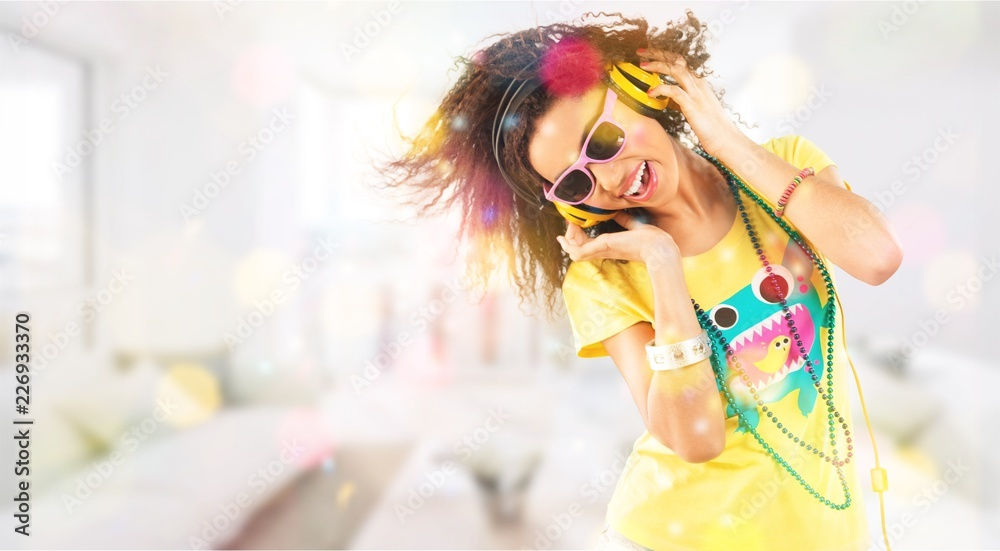 Fototapeta Happy young woman listening music in headphones