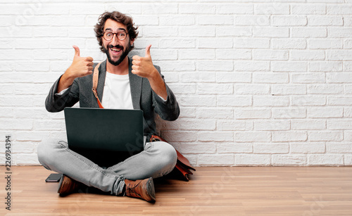 Fotografie, Obraz  young man sitting on the floor with a satisfied, proud and happy look with thumbs up, signaling OK with both hands, sending a positive, alright' message