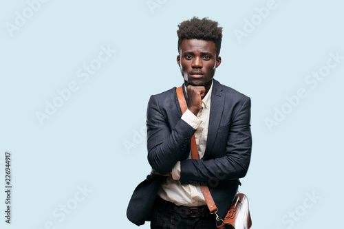 Fotografie, Tablou  young black businessman with a goofy, dumb, silly look, feeling shocked and confused at a recent realization, not really understanding an idea