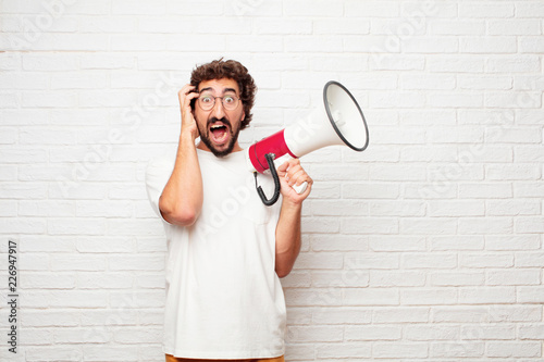 young dumb man with a crazy, amazed look of surprise, holding head with both hands, pulling hair Canvas Print