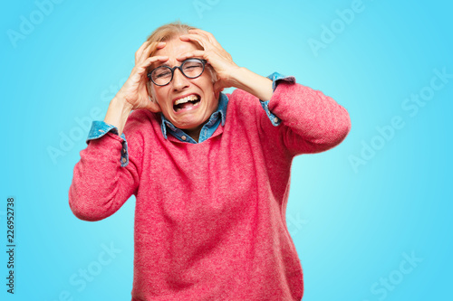 Fotografía  Beautiful adult blonde woman with a crazy, amazed look of surprise, holding head with both hands, pulling hair