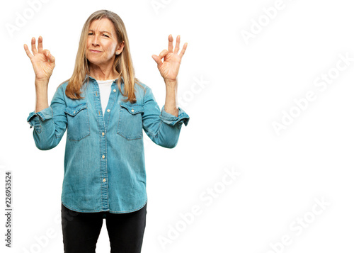 Obraz na plátně  senior beautiful woman making an alright or okay gesture approvingly with both hands, looking happy and satisfied