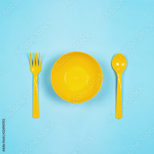 Photo  Set of empty yellow plastic tableware bowls, spoons and forks  isolated on blue pastel background